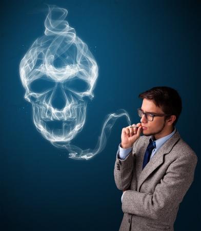 man smoking: Handsome young man smoking dangerous cigarette with toxic skull smoke Stock Photo