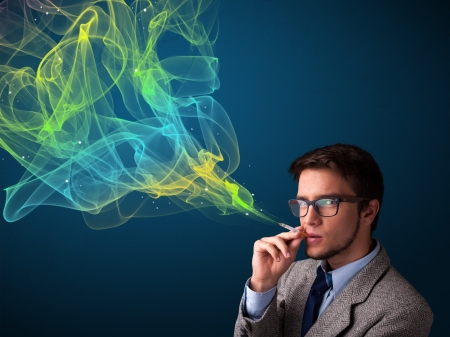 Handsome young man smoking cigarette with colorful smoke photo