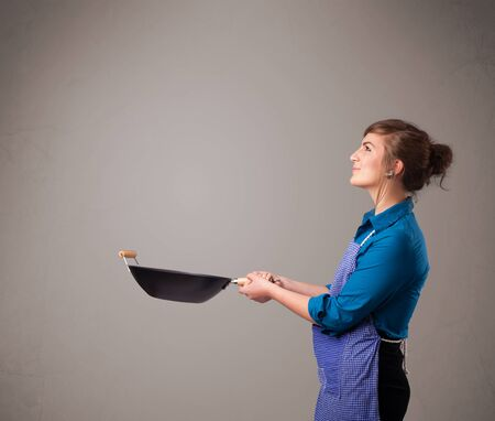 Attractive young lady holding a frying pan Stock Photo - 16748207