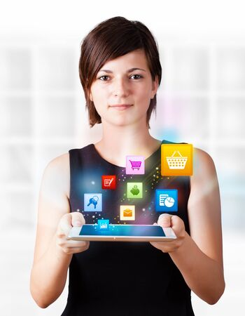 business tablet: Young business woman looking at modern tablet with colourful icons