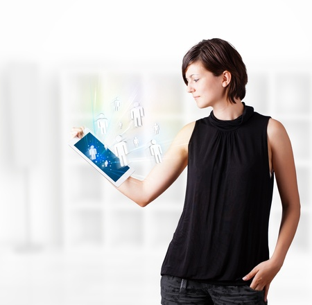 Young business woman looking at modern tablet with social icons Stock Photo - 16747368