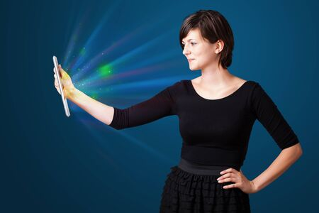 Young business woman looking at modern tablet with abstract lights  photo