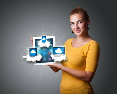 Beautiful young woman holding tablet with modern devices in clouds Stock Photo - 16750140