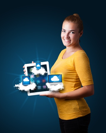 Beautiful young woman holding tablet with modern devices in clouds Stock Photo - 16750551