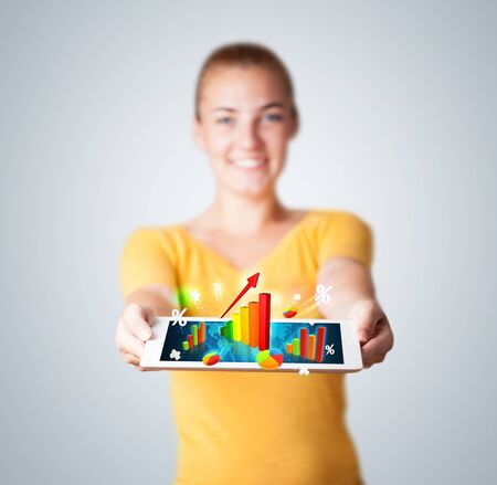 Beautiful young woman holding tablet with colorful graphs and diagrams Stock Photo - 16750108