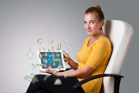 beautiful young woman holding tablet with money photo