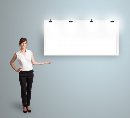 Beautiful young woman presenting modern copy space