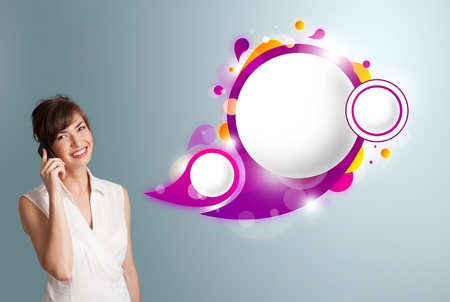 Pretty young woman presenting abstract speech bubble copy space and making phone call photo