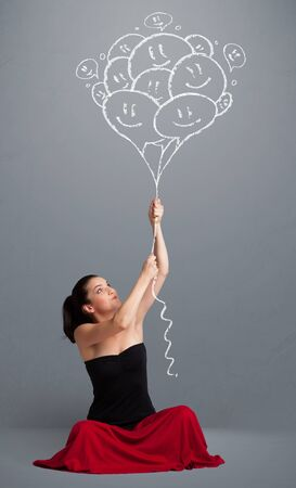 Happy young woman holding smiling balloons drawing photo