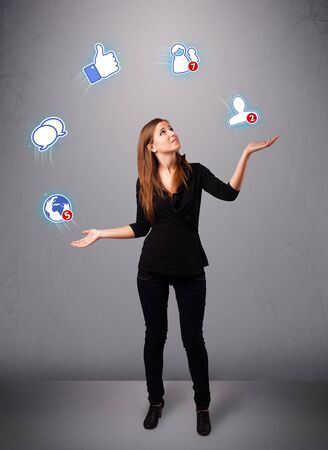 attractive young woman standing and juggling with social network icons photo