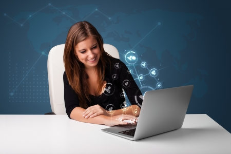 Beautiful young lady sitting at desk and typing on laptop with social network icons comming out Stock Photo - 17340181