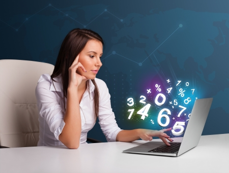 Beautiful young woman sitting at desk and typing on laptop with 3d numbers comming out photo