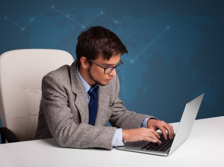 Attractive young man sitting at desk and typing on laptop photo