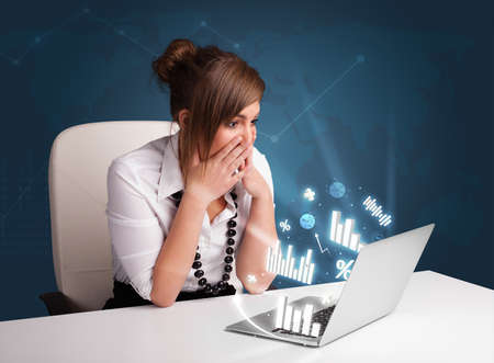 Pretty woman sitting at desk and typing on laptop with diagrams and graphs comming out Stock Photo - 17340200