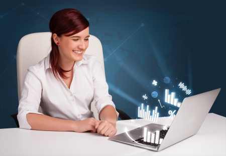 Pretty woman sitting at desk and typing on laptop with diagrams and graphs comming out Stock Photo - 17340182