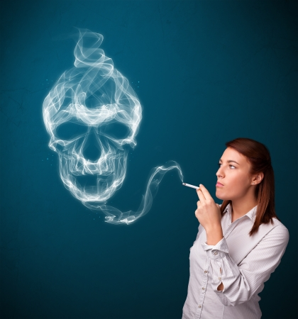 Pretty young woman smoking dangerous cigarette with toxic skull smoke  Stock Photo - 17340164
