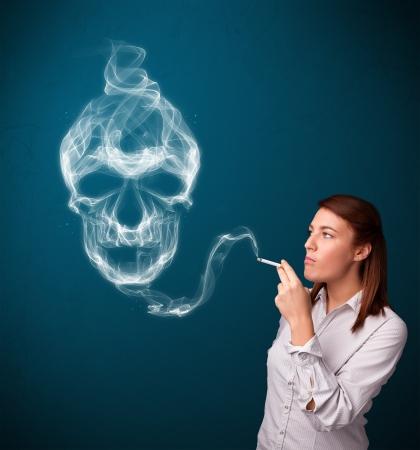 Pretty young woman smoking dangerous cigarette with toxic skull smoke Stock Photo - 17340164