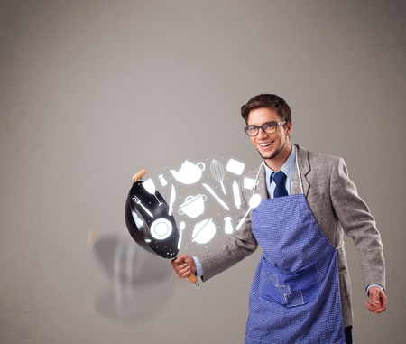 tossing: Handsome young man with kitchen accessories icons Stock Photo