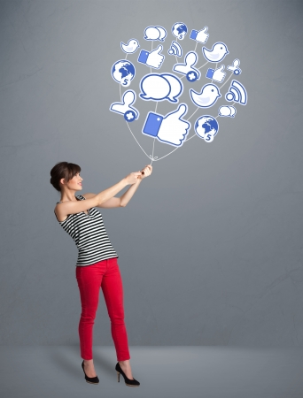 Young pretty woman holding social icon balloon photo