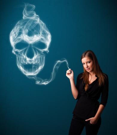 Pretty young woman smoking dangerous cigarette with toxic skull smoke Stock Photo - 17455560