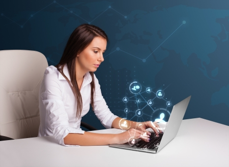 Beautiful young lady sitting at desk and typing on laptop with social network icons comming out photo