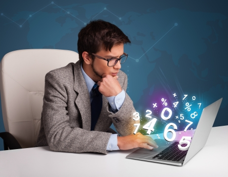 Handsome young man sitting at desk and typing on laptop with 3d numbers comming out photo