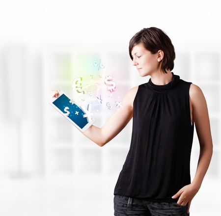 woman tablet: Young business woman looking at modern tablet with currency icons