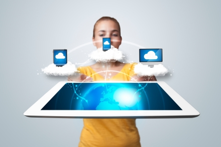 Young woman holding tablet with abstract clouds and modern devices photo