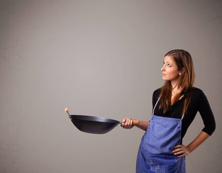 Attractive young lady holding a frying pan Stock Photo - 17563470