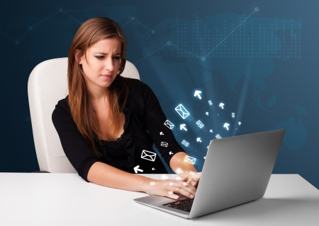 Pretty young lady sitting at dest and typing on laptop with message icons comming out Stock Photo - 17563614