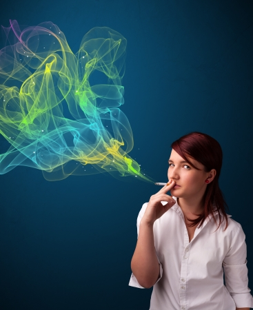 Pretty young lady smoking cigarette with colorful smoke Stock Photo - 17563578