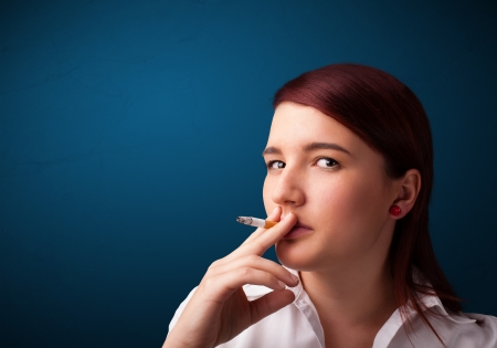 inhale: Beautiful young woman smoking cigarette with copy space Stock Photo