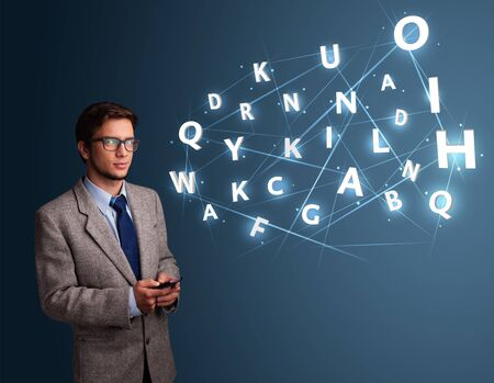 Handsome young man typing on smartphone with high tech 3d letters comming out photo