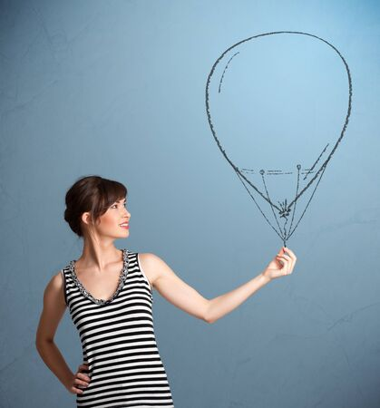 Beautiful young woman holding balloon drawing photo