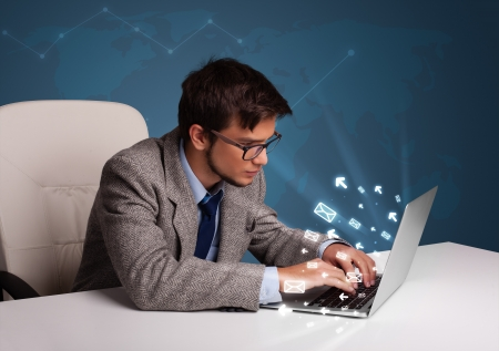 Attractive young man sitting at dest and typing on laptop with message icons comming out Stock Photo - 17737752