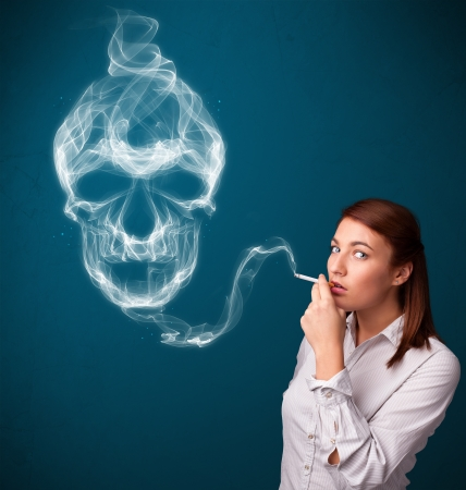 Pretty young woman smoking dangerous cigarette with toxic skull smoke  Stock Photo - 17738291