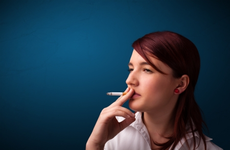 cigare: Beautiful young woman smoking cigarette with copy space Stock Photo