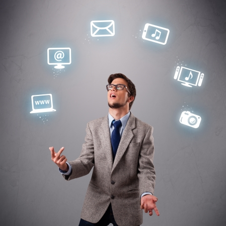 funny boy standing and juggling with electronic devices icons photo