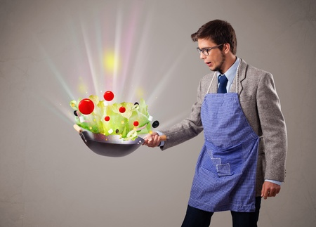 Attractive young man cooking fresh vegetables photo