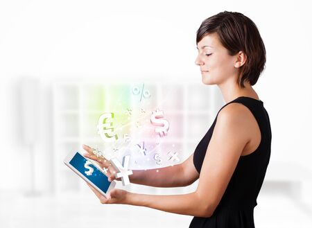Young business woman looking at modern tablet with currency icons Stock Photo - 17738281