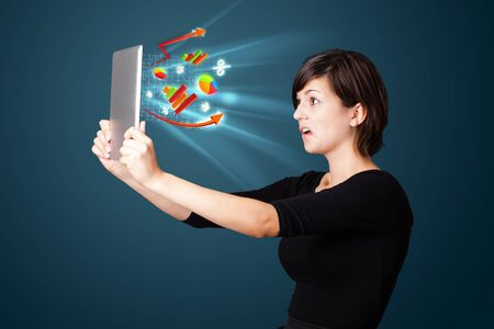 Young business woman looking at modern tablet with abstract lights and various diagrams Stock Photo - 17738389
