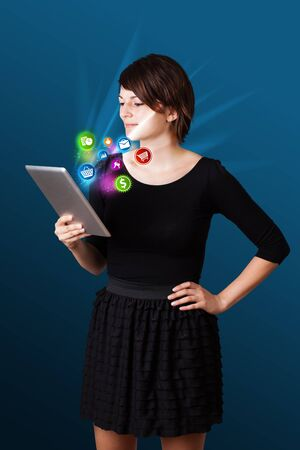 Young business woman looking at modern tablet with abstract lights and various icons Stock Photo - 17739801