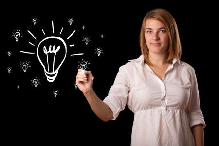 Young woman drawing light bulb on whiteboard photo
