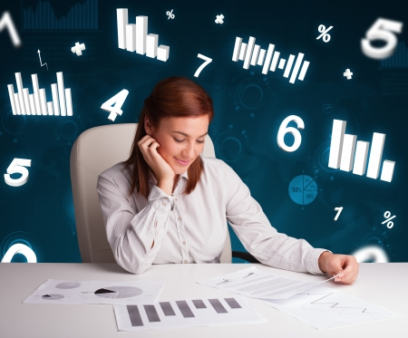 Pretty young businesswoman sitting at desk with diagrams and statistics photo