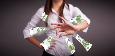 Pretty young woman standing and throwing money Stock Photo - 17784580