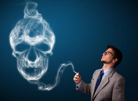 fumando: Apuesto joven peligroso fumar cigarrillos con humo tóxico cráneo