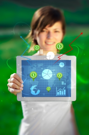 woman holding money: Young business woman looking at modern tablet with abstract light and various diagrams