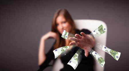 Pretty young woman sitting and throwing money Stock Photo - 17895129