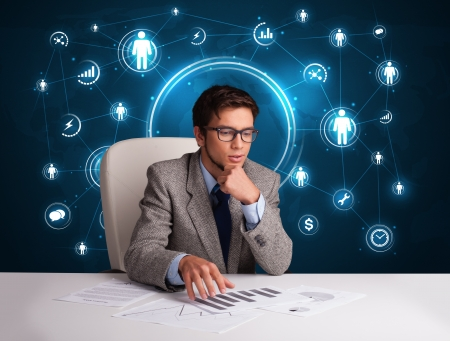 Young businessman sitting at desc with social network icons photo