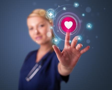 Joven enfermera de pie y presionando tipo médico moderno de botones Foto de archivo